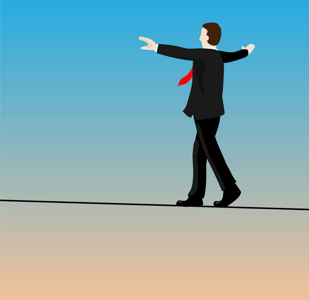 stock image of business man walking tightrope